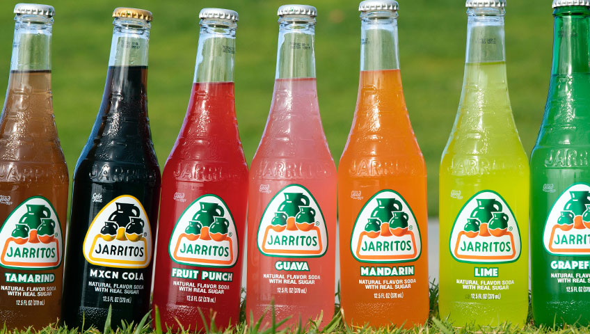 Jarritos labeled craft soda bottles in a straight line.