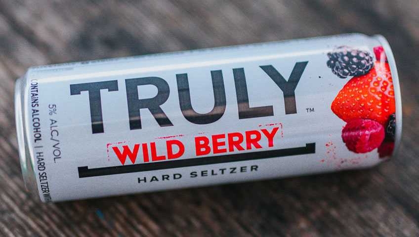 Truly wild berry hard seltzer can laying faceup on wooden surface.