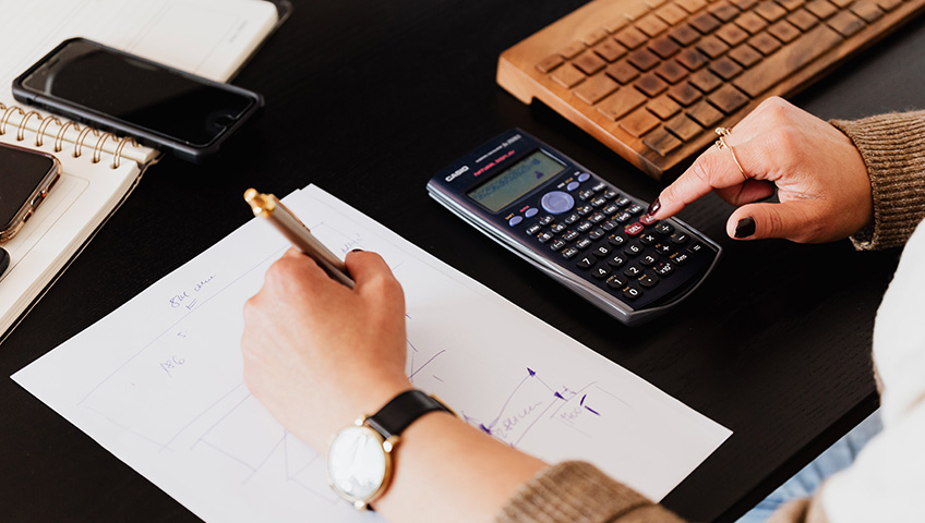 Business owner doing calculations to figure cost of custom product labels.