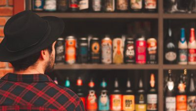 Male consumer staring at several shelves full of craft beer options and observing label design.