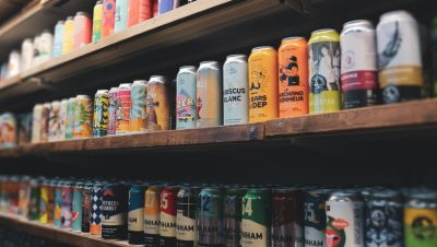 Three shelves in a retail store full of various craft beer cans with shrink sleeve and pressure-sensitive can wraps.