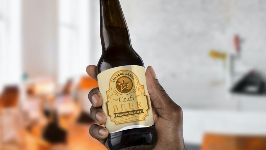 Hand holding craft beer bottle with creased, peeling label.