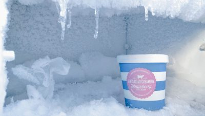 Ice cream container with cold-resistant label surrounded by ice in freezer.