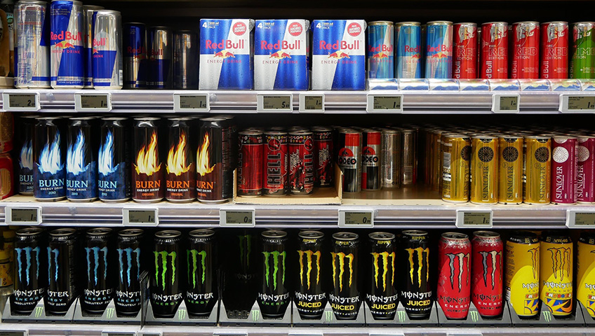 Three shelves in a supermarket full of various energy drink products displaying labels that meet legal requirements.