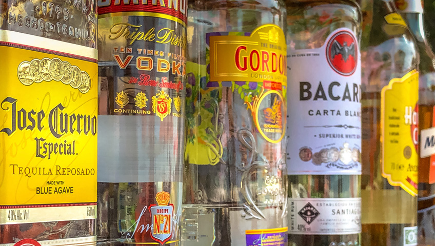 Close-up of a variety of liquor bottles with colorful labels--tequila, rum, gin, vodka.