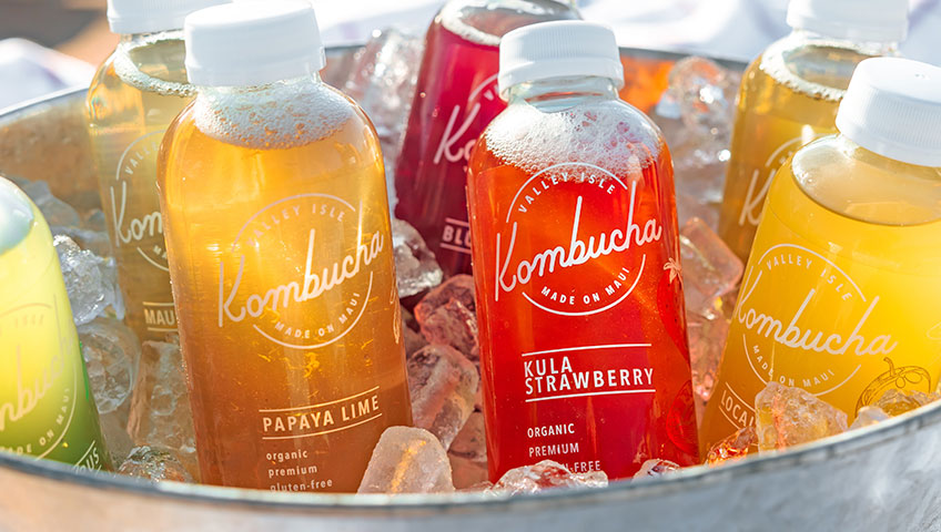 Several bottles of kombucha with labels that meet legal requirements sitting in a large bucket of ice outdoors.